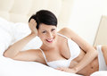 Woman in white bra is lying in the soft bed Royalty Free Stock Photos