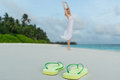 Woman in a white dress dancing on the tropical beach against flip flops closeup Royalty Free Stock Photo