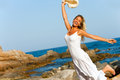 Woman in white dress jumping on beach. Royalty Free Stock Photography