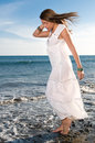 Woman in white dress near the seaside at sunset Stock Images