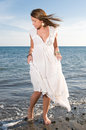 Woman in white dress near the seaside at sunset Stock Photography