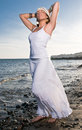Woman in white dress near the seaside at sunset Stock Image