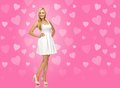 Woman in white dress over pink background beauty fashion and valentines day concept smiling and high heels with hearts Stock Photography