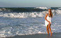 Woman in white dress posing on the sea coast Stock Image
