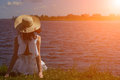 Woman in white dress sits on riverside, back view Royalty Free Stock Photo
