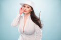 Woman in white fashion with cap showing cleavage half body shot of a pretty long hair posing sexy while looking at the camera on a Royalty Free Stock Photo
