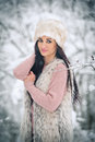 Woman with white fur cap and sheepskin  smiling enjoying the winter scenery in forest. Side view of happy brunette girl posing Royalty Free Stock Images