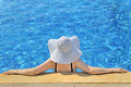 Woman with white hat relaxing at the edge pool Stock Image