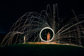 Woman in White Long Sleeve Shirt Standing in the Center of Round Firework Light