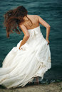 Woman in white near stormy sea full body rear view of with long hair dress standing blowing wind hair selective focus grain added Stock Photos