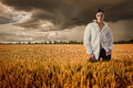 Woman in white shirt in a field of golden rye beautiful brunette is standing rural landscape with dramatic cloudy sky Stock Photo