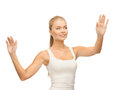Woman in white t shirt pressing imaginary button smiling blank with raised hands Stock Photos