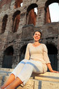Woman in white wear sitting near Colosseum Stock Image