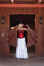 A woman with a wild west sexy in red corset and long white standing in the doorway of the old bar Royalty Free Stock Photos