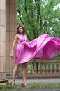 Woman in wind beautiful young model wearing pink violet silk tunic dress moving aside blowing up her dress high so that slim long Stock Images