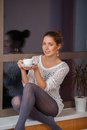 Woman on window sill portrait of a happy young relaxing at home with cup of tea the Royalty Free Stock Photos