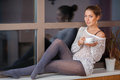 Woman on window sill portrait of a happy young relaxing at home with cup of tea the Stock Images