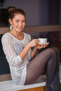 Woman on window sill portrait of a happy young relaxing at home with cup of tea the Royalty Free Stock Photo