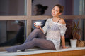 Woman on window sill portrait of a happy young relaxing at home with cup of tea the Royalty Free Stock Photography