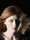 Woman with windswept hair looking down closeup of beautiful on black background Royalty Free Stock Images