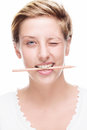 Woman winking with pencil in her mouth blonde happy on white background Royalty Free Stock Images