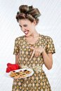 Woman winks as she holds plate of cookies portrait young in a patterned dress points to the baked Stock Images