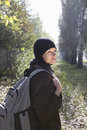 Woman in winter clothing with backpack at park side view of a beautiful young Royalty Free Stock Photos