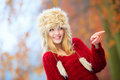 Woman in winter clothing fur cap autumn or fashion happy young wearing fashionable wintertime clothes outdoor pointing with finger Royalty Free Stock Image