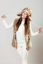 Woman in winter clothing fur cap fashion happy young wearing fashionable wintertime clothes studio shot on gray background Royalty Free Stock Photography