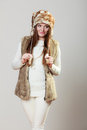 Woman in winter clothing fur cap fashion happy young wearing fashionable wintertime clothes studio shot on gray background Stock Image