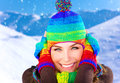 Woman on winter holidays closeup portrait of pretty closing ears from frosty wind wearing colorful wool hat and gloves spending in Stock Image