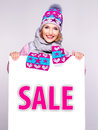 Woman in winter outerwear holds the white banner with sale word adult smiling on it Royalty Free Stock Photo