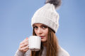 Woman in winter wool cap drinking tea attractive long hair girl holds mug with hot beverage warming herself studio shot on blue Stock Images