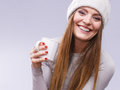 Woman in winter wool cap drinking tea attractive long hair girl holds mug with hot beverage warming herself studio shot on gray Stock Photography