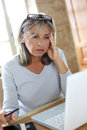 Woman wit grey hair working with a worried look perplexed senior in front of laptop Royalty Free Stock Images
