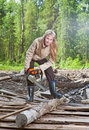 Woman in wood saws a tree a chain saw Royalty Free Stock Photo