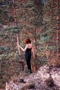 Woman on wooded cliff Stock Photography