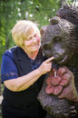 Woman and wooden bear smiling middle aged playing with Stock Photography