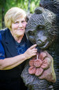 Woman and wooden bear smiling middle aged playing with Royalty Free Stock Image