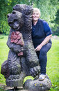 Woman and wooden bear smiling posing with Stock Photos