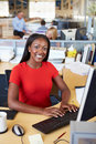 Woman working at computer in modern office smiling Stock Photo