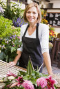 Woman working at flower shop smiling Royalty Free Stock Photos