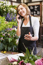 Woman working at flower shop using telephone Stock Image
