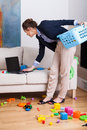 Woman working on her laptop during cleaning up living room young elegant Royalty Free Stock Photo