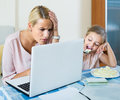 Woman working from home little daughter asking for attention stressed women focus on Royalty Free Stock Images