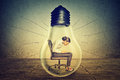 Woman working on laptop computer sitting inside electric light bulb Royalty Free Stock Photo