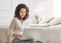 Woman working on a laptop happy casual beautiful sitting the bed in the house Royalty Free Stock Photos