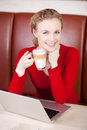 Woman working with laptop while having coffee break in café Royalty Free Stock Photo
