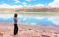 Woman working on mobile phone the at the shore of lagoon celeste bolivia Royalty Free Stock Photography