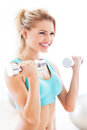 Woman working out with dumbbells in gym exercising Stock Images